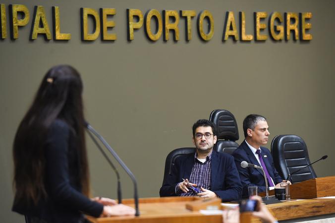 Vereadores dialogam com Secretário municipal de Educação, Adriano Naves de Brito. Na foto, a vereadora Carolina Rousseff (ao microfone), o secretário Adriano e o vereador Cassio Trogildo respectivamente.
