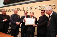 Nereu (c) entrega diploma a André Lico (d), pároco da Igreja da Glória Foto: Elson Sempé Pedroso