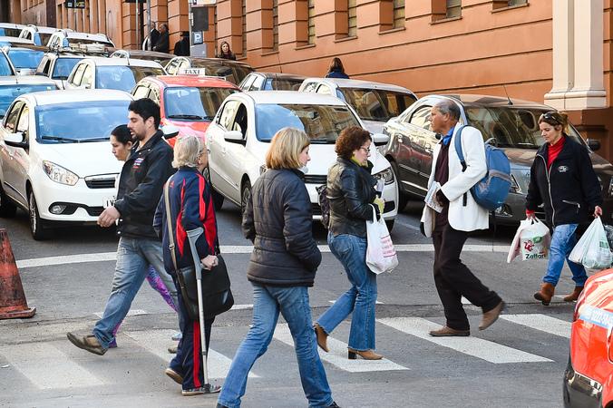 Pedestres atravessam faixa de segurança.