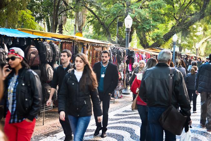 Pedestres caminham junto a bancas de artesanato da Praça da Alfândega