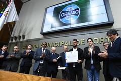 Presidente Romildo Bolzan e jogador Maicon receberam diplomas entregues por Tarciso Flecha Negra (e)