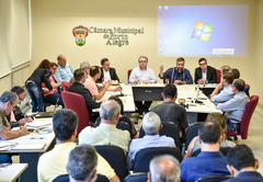 Informações sobre cumprimento da Lei dos Táxis. Representantes da EPTC e associações de taxistas na mesa e platéia.