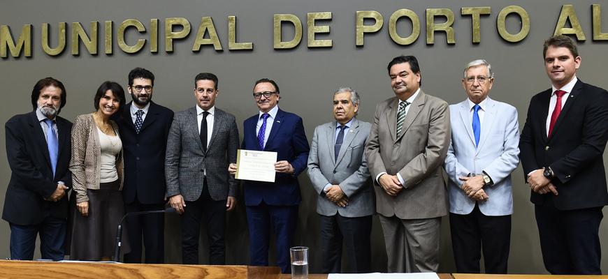 Vice-reitor segura o diploma conferido à PUCRS pela Câmara Municipal