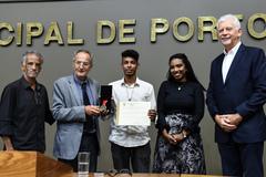 Danyel Oliveira (c) recebe a Comenda e o diploma entregues por Ferronato (e)