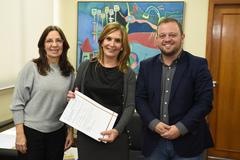Mônica Leal (c) recebeu das mãos da coordenadora do GISA o documento para realização do convênio