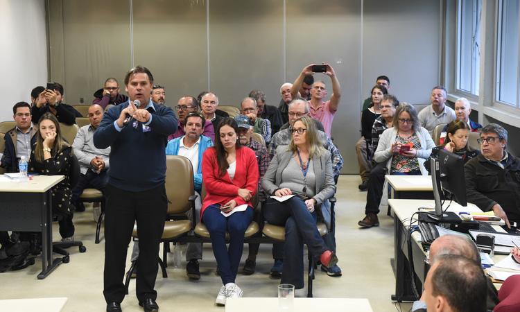 """Reunião para debater a """"Lei Geral dos Táxis"""". Ao microfone, Gerson Port, taxista."""