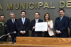 Thompson Flores (c) recebe o diploma entregue pela vereadora Mônica Leal (PP)