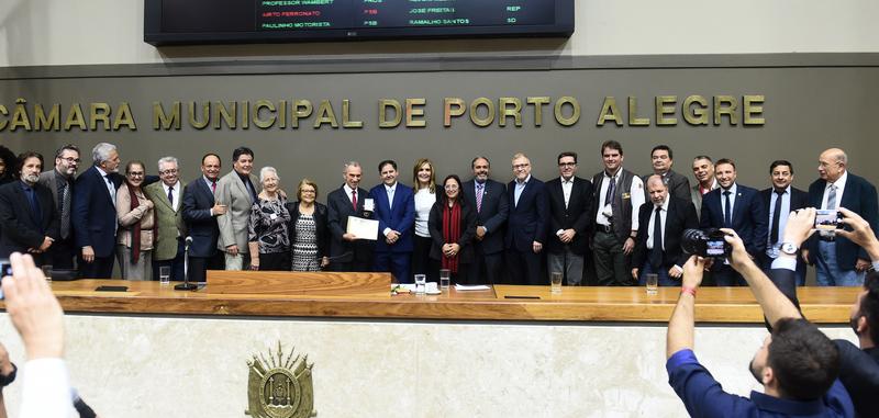 Período de Comunicações em homenagem ao jornalista Lauro José de Quadros, com a outorga da Comenda Porto do Sol. Na foto, o homenageado e vereadores (Foto: Ederson Nunes/CMPA)