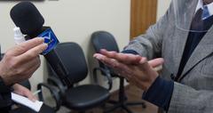 Presidente da CMPA, vereador Reginaldo Pujol, promulga a Lei de publicidade das empenas cegas, de autoria da vereadora Mônica Lea. Na foto, vereador Pujol higieniza as mãos antes de empunhar o microfone da TV Câmara