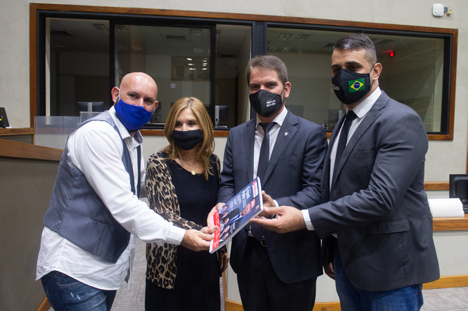 Presidente Marcio Bins Ely e vereadores Monica Leal e Alexandre Bobadra recebem exemplar da revista Em Evidência.