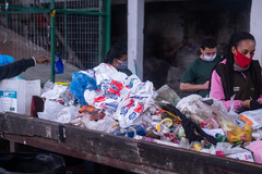 Trabalhadores fazem separação do material na esteira de reciclagem da Coopertuca
