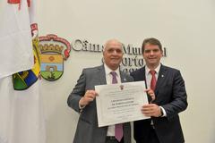 Marcelo Medeiros (e) recebe o título entregue por Márcio Bins Ely (PDT)