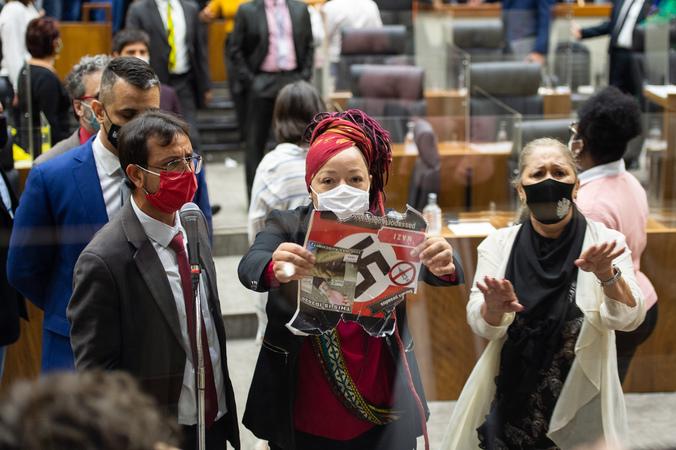 """Sessão ordinária - Movimentação de plenário. Na foto, vereadora Daiana Santos com um cartaz que os manifestantes contrários ao """"passaporte vacinal"""" seguravam nas galerias. (Foto: Elson Sempé Pedroso/CMPA)"""