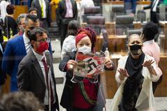 """Movimentação de plenário. Na foto, vereadora Daiana Santos com um cartaz que os manifestantes contrários ao """"passaporte vacinal"""" seguravam nas galerias."""