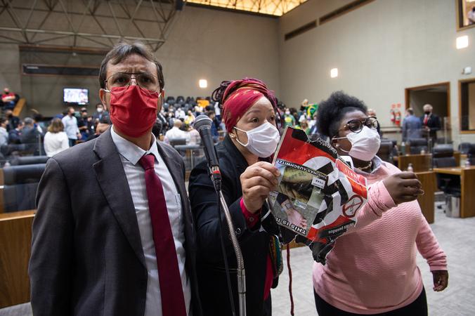 """Sessão ordinária - Movimentação de plenário. Na foto, vereadores Jonas Reis, Daiana Santos e Laura Sito com um dos cartazes que os manifestantes contra o """"passaporte vacinal"""" seguravam nas galerias. (Foto: Ederson Nunes/CMPA)"""